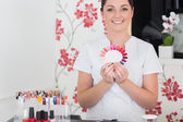 Smiling woman holding nail shades at salon — Stock Photo