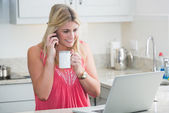 Happy woman with laptop and coffee cup on call in kitchen — Stock Photo
