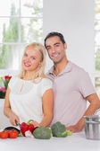 Smiling blonde woman cooking with her husband — Stock Photo