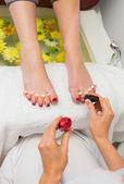 Woman applying nail varnish to toe nails at spa center — Stock Photo