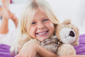 Blonde girl embracing her teddy bear — Stock Photo