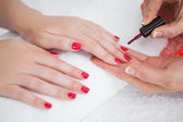 Woman applying nail varnish to finger nails — Stock Photo