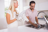 Happy couple washing dishes together — Stock fotografie
