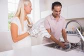 幸福的情侣洗盘子在一起 — 图库照片