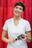 Young woman with hairbrush over red backdrop — Stok fotoğraf