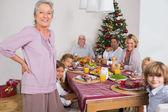 Grandmother standing beside dinner table — Stock Photo