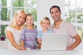 Happy family using a laptop together — Stock Photo