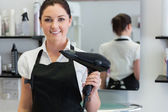 Female hairdresser holding hair dryer — Stock Photo