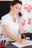 Woman answering phone at nail salon — Stock Photo
