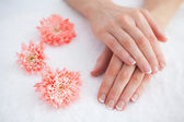 Flowers with french manicured fingers at spa center — Stock Photo