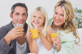 Family drinking glasses of orange juice — Stock Photo