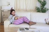 Happy woman on couch with bowl at home — Stock Photo