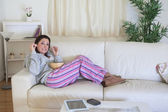 Bored woman having popcorn on couch at home — Stock Photo