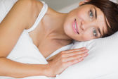Beautiful woman smiling in bed — Stock Photo