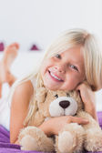 Smiling girl with her teddy bear lying on a bed — Stok fotoğraf
