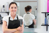 Hairdresser with hair brush in hairdressing salon — Stock Photo