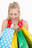 Cute excited woman looking into her shopping bags — Stock Photo