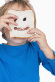 Boy looking through holes in bread slice — Stock Photo