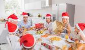 Lachende familie rond de tafel met kerstmis — Stockfoto