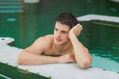 Smiling man relaxing in the pool — Stock Photo