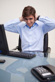Business man covering ears at office desk — Stock Photo