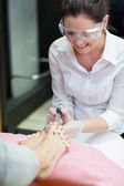 Nail technician removing callus at feet — Stock Photo