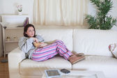 Relaxed woman with popcorn bowl watching tv — Stock Photo
