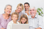 Family smiling in front of a laptop screen — Stock Photo