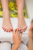 Woman polishing toe nails at spa center — Stock Photo
