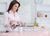 молодая женщина разлива кофе — Стоковое фото