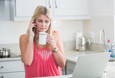 Woman with laptop and coffee cup on call in kitchen — Stock Photo