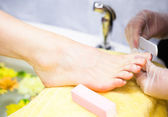 Close-up of nail technician filing woman's toe nails — Stock Photo