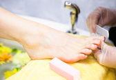 Close-up of nail technician filing woman's toe nails — Stock Photo