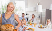 Blonde woman showing the roast turkey — Stockfoto