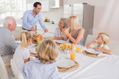 Smiling father proposing a slice of turkey — Stock Photo