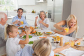Happy family raising their glasses together — Stock Photo