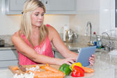 Woman cooking whilst looking at digital tablet in kitchen — Stock Photo