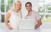 Smiling couple using laptop — Stock Photo