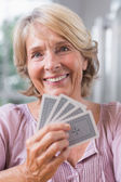 Close up of a smiling woman playing cards — Stock Photo