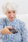 Elderly focused woman using the remote — Stock Photo