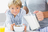Father pouring milk for sons cereal — Stock Photo