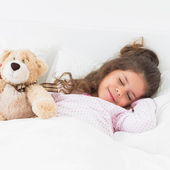 Little girl sleeping with teddy bear — Stock Photo