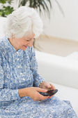 Elderly happy woman using a smartphone — Stock Photo
