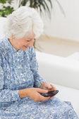 Elderly happy woman using a smartphone — Stock Photo