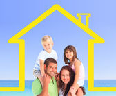 Smiling family posing with a yellow house illustration — Stock Photo