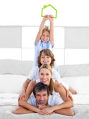Jolly family having fun with green house illustration — Stock Photo