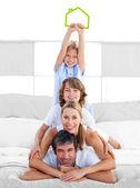 Jolly family having fun with green house illustration — Stock Photo