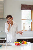 Woman calling in her kitchen — Stock Photo