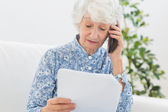Elderly woman reading papers on the phone — Stock Photo