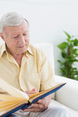 Elderly man watching his pictures — Stock Photo